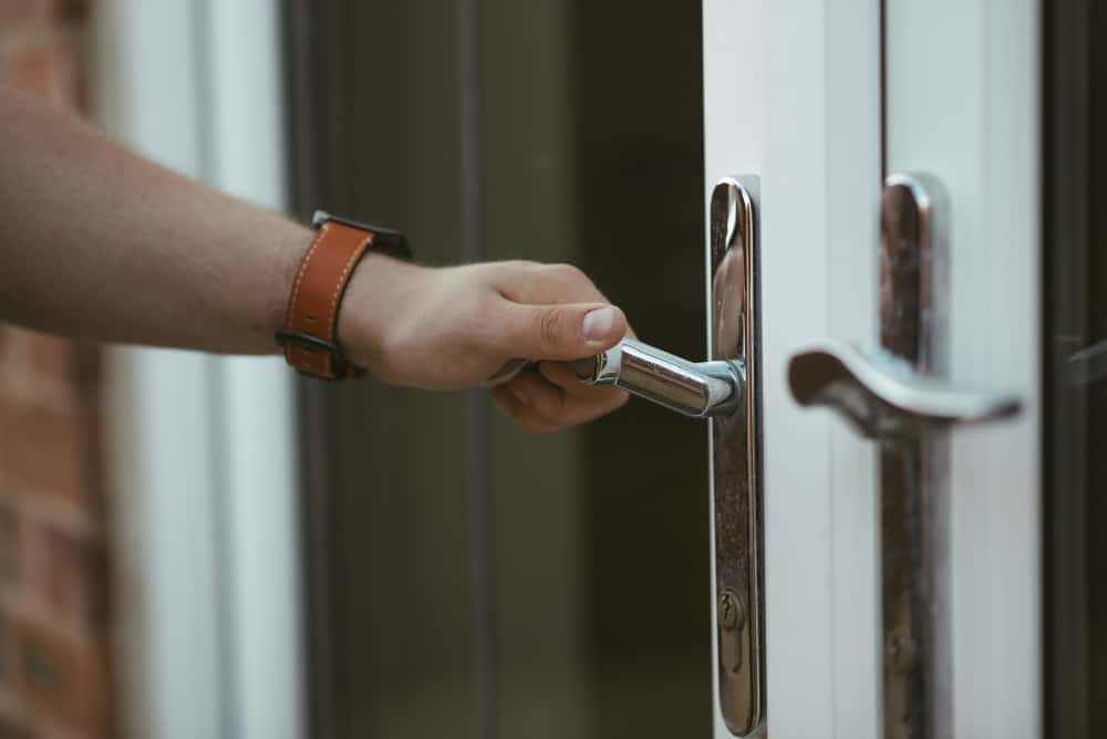 closeup shot person holding door knob opening door 1