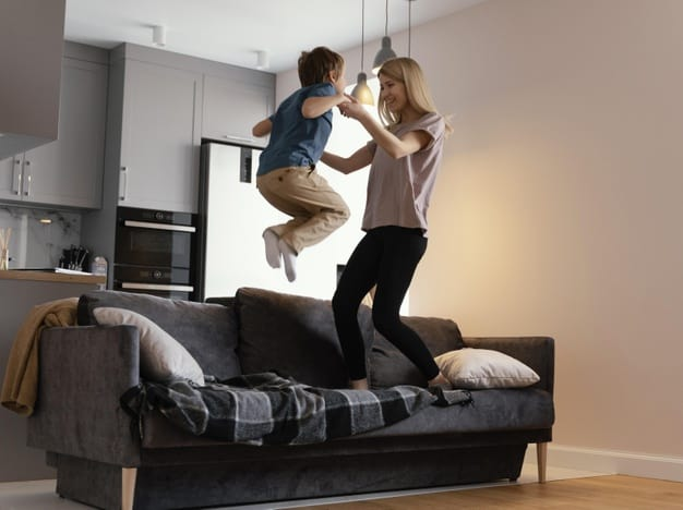 full shot mother kid jumping couch 23 2148920128
