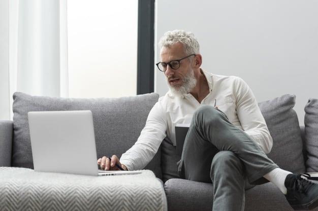 senior man home studying laptop taking notes 23 2148991562